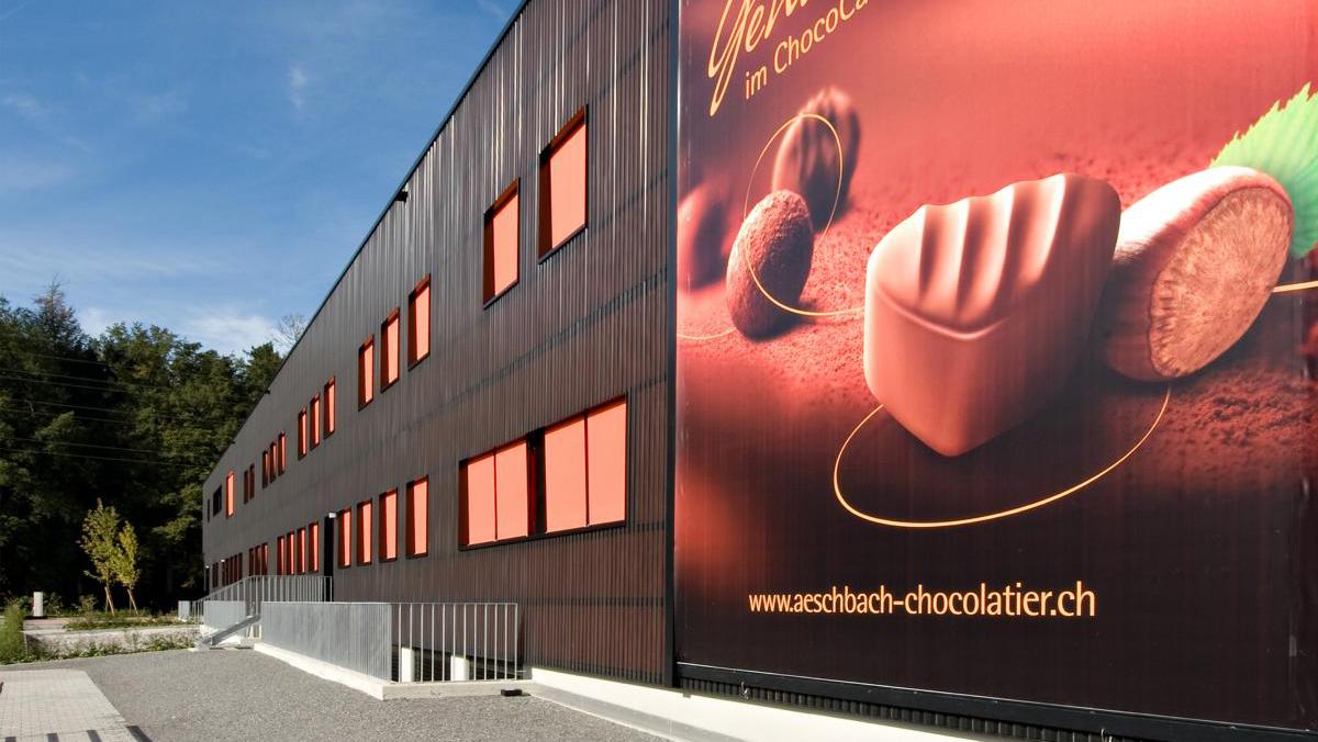 PR Kampagne Chocodromo: Der Firmenhauptsitz von Aeschbach Chocolatier mit einem Werbebanner. Aeschbach Chocolatier verlegt seinen Firmenhauptsitz in den Kanton Luzern und nutzt den Neubau am neuen Standort, um sein Angebot mit neuen Geschäftsbereichen insbesondere im Eventbereich zu erweitern. Diese neuen Entwicklungen werden im Rahmen einer PR-Kampagne kommuniziert.