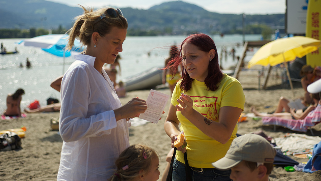 Traditionelle PR Water Safety Run: Tourleiterin der Water-Safety-Kampagne mit der Kampagnenbekleidung. Beim erklären des Themas Wassersicherheit in Schweizer Badis. Die Verhaltensregeln, welche Ertrinkungsunfälle verhindern wird durch den Water-Safety-Run den Eltern und Betreuungspersonen sowie Kindern Kommuniziert.